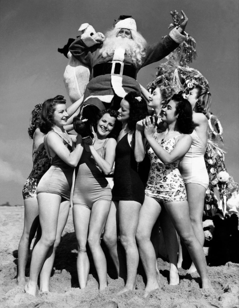 SANTA CLAUS posing surrounded by pretty young things in bathing suits on the beach of Venice, California, on December 4, 1939. In fact, it is Fred ROBERTS, a shoe seller who made a fortune. Dressed as Santa Claus, he shared his wealth by organizing a Christmas party to which hundreds of children were invited. Le PERE NOEL pose entouré de jolies jeunes femmes en maillot de bain, sur la plage de Venice en Californie, le 4 décembre 1939. Il s'agit en fait de Fred ROBERTS, un commerçant en chaussure qui a fait fortune. Celui-ci, déguisé en Père Noël, profite alors de sa fortune en organisant une fête de Noël à laquelle sont conviés des centaines d'enfants.