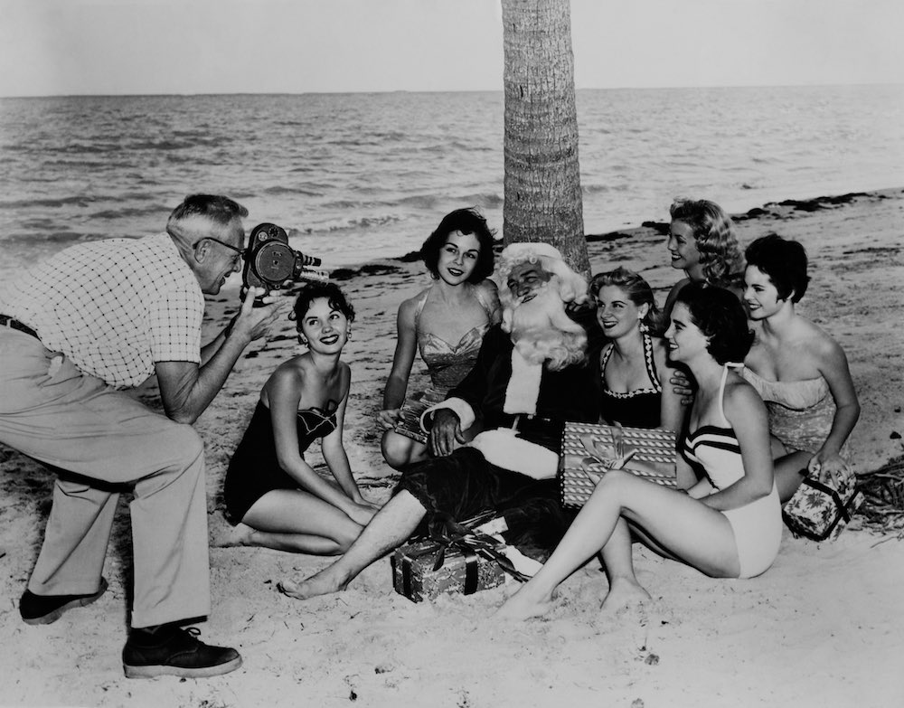 UNITED STATES - JANUARY 01: Santa Claus On The Beach Surrounded By Young Women In Swimsuit In Miami Beach During Sixties (Photo by Keystone-France/Gamma-Keystone via Getty Images)
