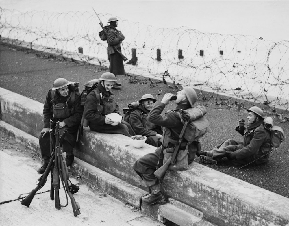 British soldiers tuck into a Christmas pudding at their post on the British coast, during the second Christmas of World War II, 26th December 1940. (Photo by David Parker/Fox Photos/Hulton Archive/Getty Images)